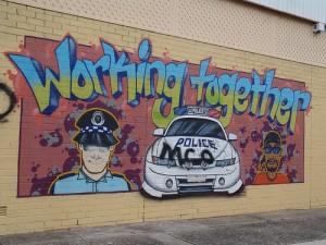 graffiti met politieagent, politieauto en de tekst 'working together'