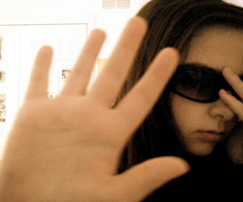 Meisje met zonnebril die camera blokkeert met haar hand